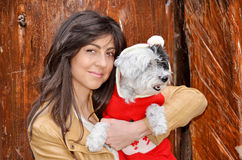 Woman hugging her dog  dressed with red christmas hats Royalty Free Stock Image