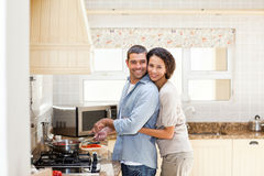 Woman hugging her husband while he is cooking Stock Photo