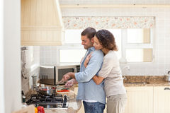 Woman hugging her husband while he is cooking Royalty Free Stock Photo
