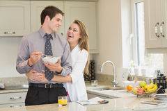 Woman hugging her husband while eating cereal Royalty Free Stock Photography