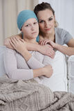 Woman hugging her ill sister Stock Photo