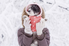 Woman  hugging her small white dog in the winter forest .snowing time Royalty Free Stock Images