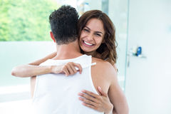 Woman hugging husband while holding pregnancy kit Stock Photos