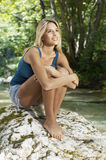 Woman Hugging Knees While Looking Away By Forest River Stock Images