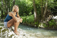 Woman Hugging Knees While Looking Away By Forest River Royalty Free Stock Images