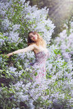 Woman hugging lilac bush. Beautiful woman in a spring garden with blooming lilacs, woman hugging lilac bush Royalty Free Stock Photography