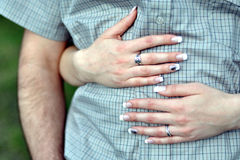 Woman hugging man. Closeup of the arms of a woman hugging a man around the waist Stock Image