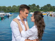 Woman hugging man against the backdrop of boats Royalty Free Stock Photo