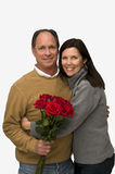 Woman Hugging Man With Red Roses. A smiling woman hugs a man who is holding a bouquet of red roses Royalty Free Stock Photo