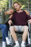 Woman hugging man in wheelchair and looking sad stock photography