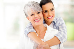 Woman hugging mother. Happy young women hugging middle aged mother at home Stock Photo