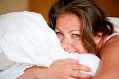 Woman hugging a pillow in bed Royalty Free Stock Photography