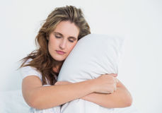 Woman hugging pillow sitting on her bed Stock Photo