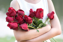 Woman hugging red roses with pleasure. Royalty Free Stock Photo