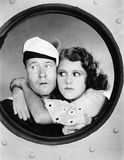 Woman hugging sailor at porthole Stock Images