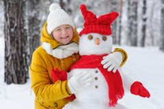 Woman hugging a snowman in winter Park. Stock Image