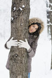 Woman hugging a tree in the winter forest .loving nature Royalty Free Stock Images