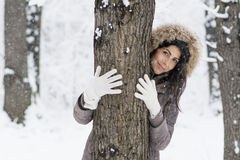 Woman hugging a tree in the winter forest .loving nature Stock Photography
