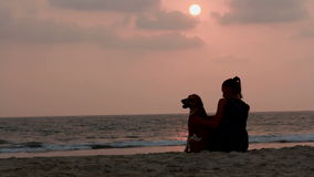 Woman hugs her dog at sunset. Silhouette of a woman is sitting outside, hugs her dog at sunset stock footage