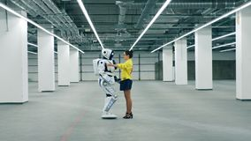 A woman hugs meets her friend robot, hugging it. stock footage