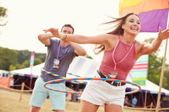 Woman with hula hoop at a music festival, man in background Royalty Free Stock Photos