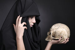 Woman with a human cranium in black. Woman with a pale face in black with human cranium. Scary woman with a pale face with human cranium. Studio shot on black royalty free stock photo