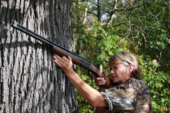 Woman hunter. Taking aim with a shot gun Stock Photo