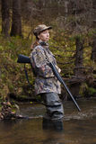 Woman hunter with gun looking into the distance Royalty Free Stock Photography