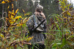Woman hunter with gun on the riverside Royalty Free Stock Photo