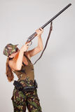 Woman hunter with a gun take aim. Gray background Stock Photography