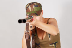 Woman hunter with a gun take aim. Gray background Royalty Free Stock Photography