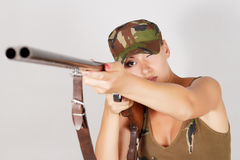 Woman hunter with a gun take aim. Gray background Royalty Free Stock Image