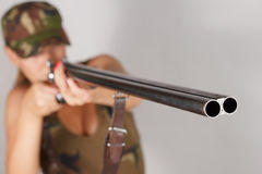 Woman hunter with a gun take aim. Gray background Stock Images