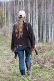 Woman hunter with gun walking in the forest. Woman hunter with shotgun walking in spring forest Royalty Free Stock Photo