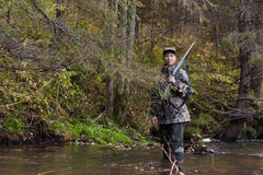 Woman hunter on the river. Woman hunter in camouflage with gun on the river Royalty Free Stock Photography