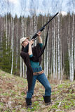 Woman hunter shooting from a gun Stock Photos
