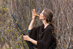 Woman hunter in shrubs with a wooden duck call Stock Image