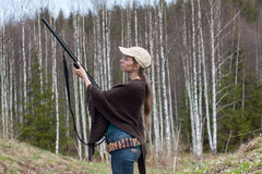 Woman hunter  takes aim from a gun in the forest Royalty Free Stock Image