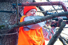 Woman hunter in a treestand. A woman hunter sits high up in a treestand with her rifle on a shooting bar. She is wearing hunter's orange Royalty Free Stock Photos