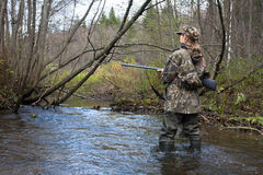 Woman hunter in waders crossing the forest river. Woman hunter in camouflage with gun crossing the river Stock Photo