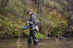 Woman hunter in waders crossing the river. Woman hunter in camouflage with gun crossing the river Stock Image