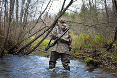 Woman hunter in waders crossing small river in the forest. Woman hunter in camouflage with gun crossing the river Royalty Free Stock Photos