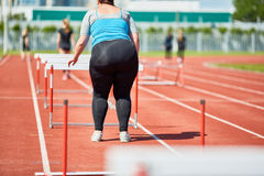 Woman by hurdle. Rear view of overweight female standing by hurdle on stadium Royalty Free Stock Image