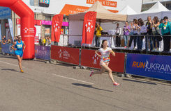 Woman hurry to finish line during Interipe  Dnipro Half Marathon race on the city street. DNEPR, UKRAINE - MAY 22, 2016:Woman hurry to finish line during Stock Photos