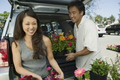 Woman with husband  Loading flowers into back of SUV portrait Stock Photography