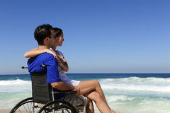 Woman and husband in wheelchair on the beach Royalty Free Stock Photos