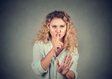 Woman with hush be quiet gesture  on gray background. Woman with hush be quiet with finger on lips gesture Royalty Free Stock Photo