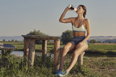 Woman hydrating after run. Attractive young lady in summer sportswear drinks water or energizing shake after the morning run while resting on a rustic wooden Royalty Free Stock Images