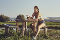 Woman hydrating after run. Attractive young lady in summer sportswear holding water plastic bottle and resting at a rustic wooden table on the bank of a river Stock Images