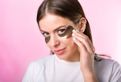 Woman with hydrogel eye patches. Young caucasian woman applying hydrogel eye patches royalty free stock photo